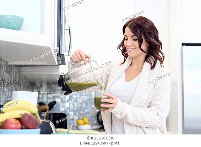 Caucasian woman pouring green juice smoothie in domestic kitchen