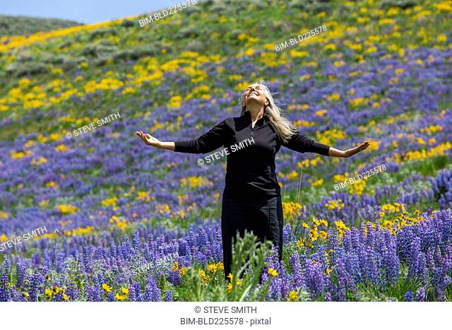 Caucasian woman smiling on hillside with wildflowers