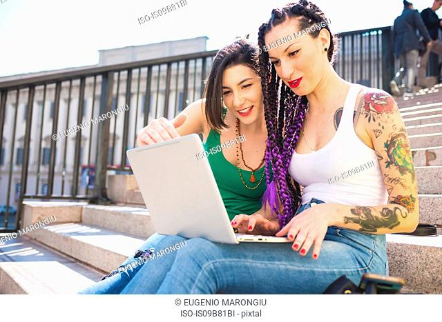 Women on city break using laptop, Milan, Italy
