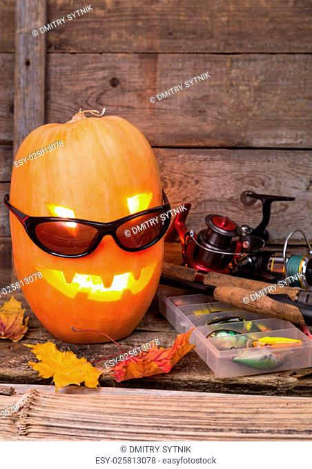 halloween pumpkin head in eyeglass with fishing tackles on wooden boards background
