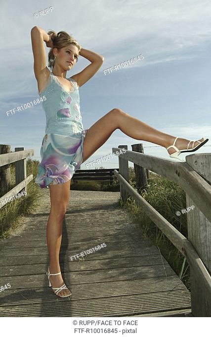 A woman wearing a stylish dress poses against the camera