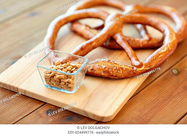 food, baking and cooking concept - close up of peanuts and pretzels on wooden table