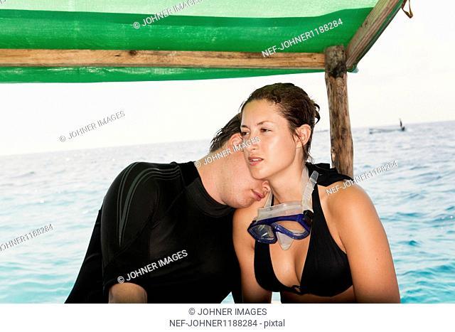 Couple in swimwear relaxing on boat