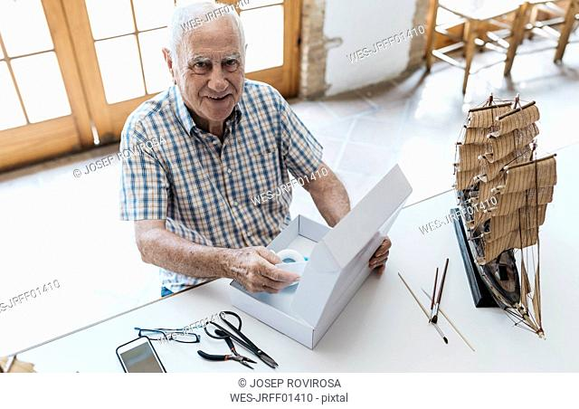 Portrait of confident senior man unpacking package with model ship on table