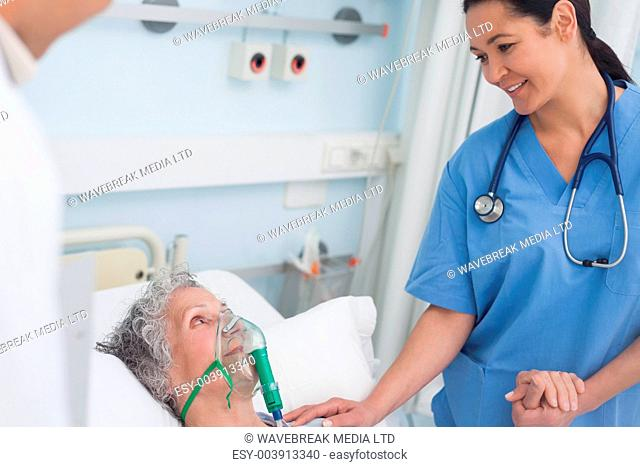 Nurse touching the hand of a patient in hospital ward