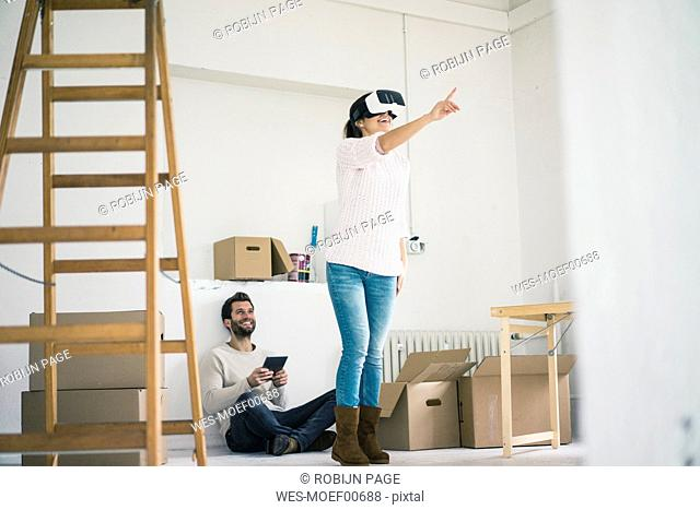 Couple in new home with woman wearing VR glasses