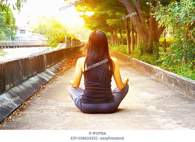 women meditating in street park and sunset nature background, warm color tone