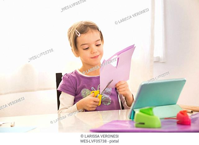 Little girl tinlering at home, cutting paper with online instructions