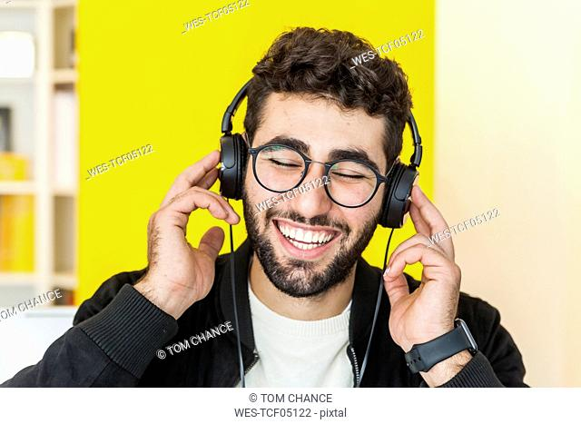 Portrait of laughing man with listening music with headphones