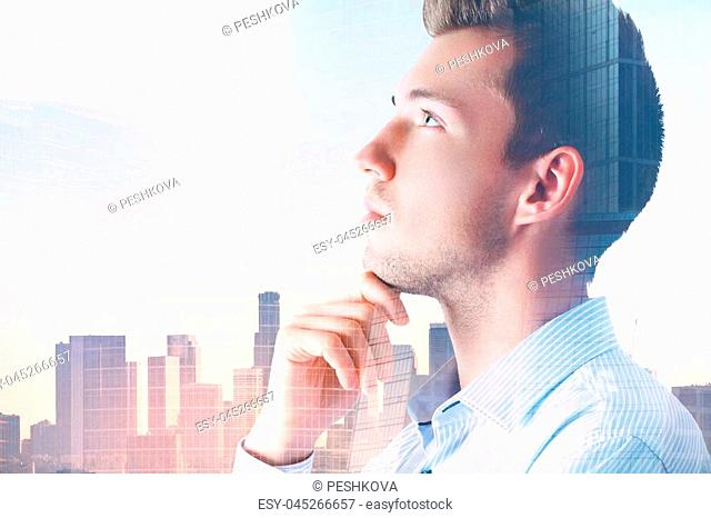 Portrait of attractive pondering young businessman on abstract city background with copy space. Employment and success concept. Double exposure