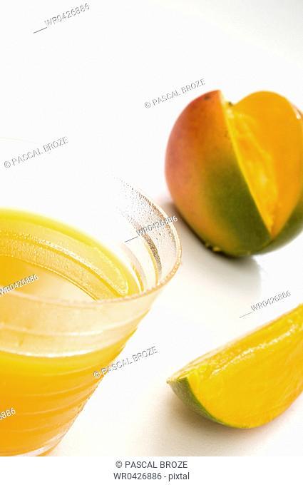 Close-up of a glass of mango juice with a mango