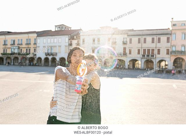 Italy, Padua, two young women with soap bubble machine