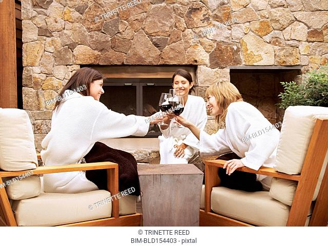 Women toasting with red wine on spa deck