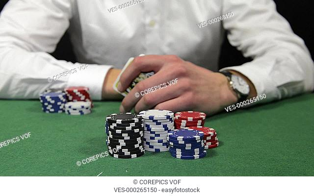 Poker player winning the pot with a pair of tens, sitting back and folding his arms