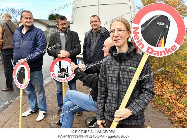 13 November 2018, Thuringia, Erfurt: Erfurters demonstrate during the laying of the foundation stone for a new mosque with a symbolic prohibition sign for...