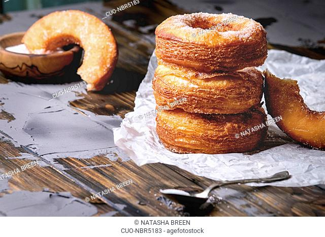 Homemade puff pastry deep fried donuts or cronuts in stack with sugar standing on crumpled paper over dark wooden concrete table