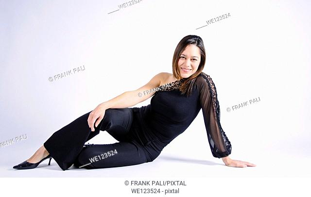Young woman of filipino ethnicity sitting sideways on a white background She has her arm on her leg