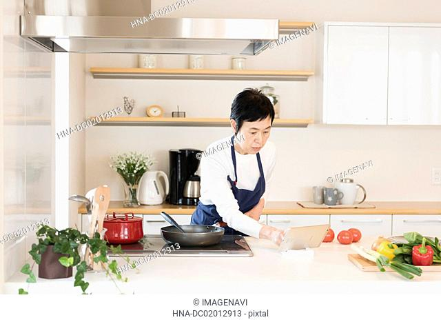 Senior woman cooking with tablet PC