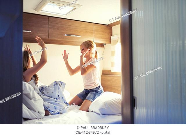 Girls playing pat-a-cake inside motor home
