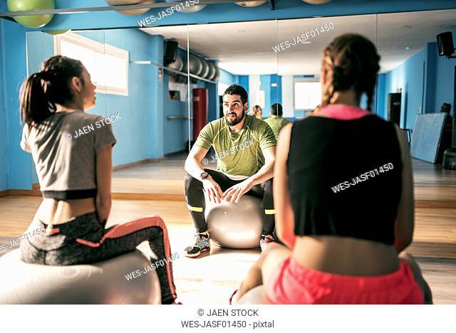 Gym coach explaining exercises to women