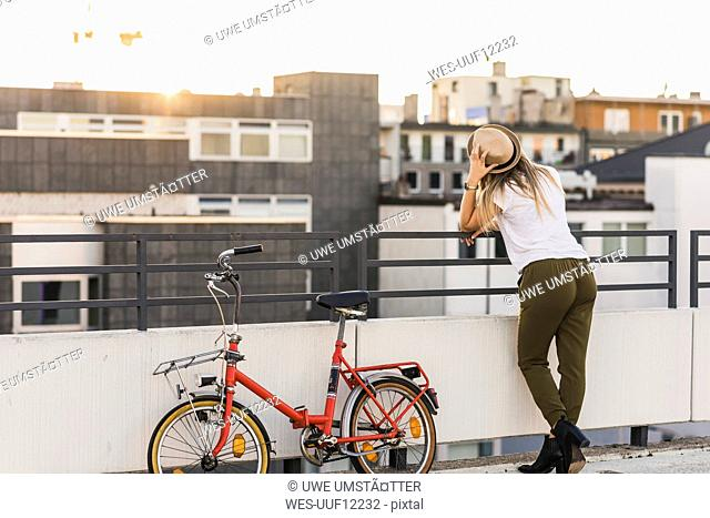 Young woman with bicycle leaning against railing
