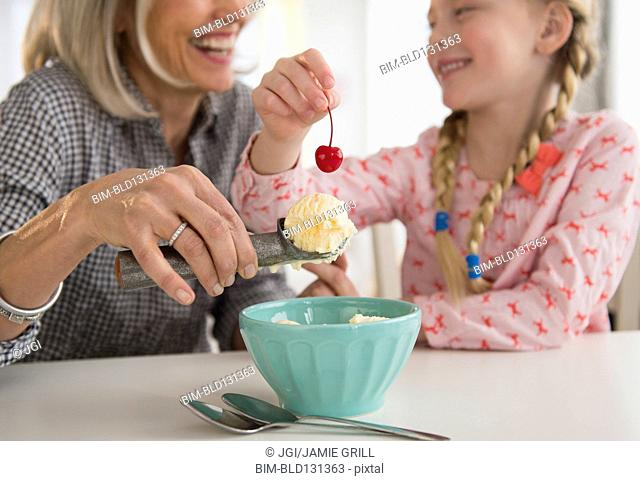 Senior Caucasian woman and granddaughter making ice cream sundae