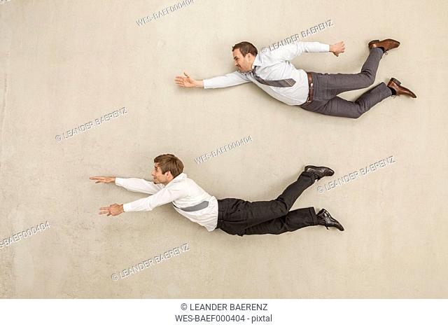 Businessmen flying against beige background