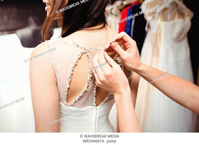 Woman trying on wedding dress with the assistance of creative designer