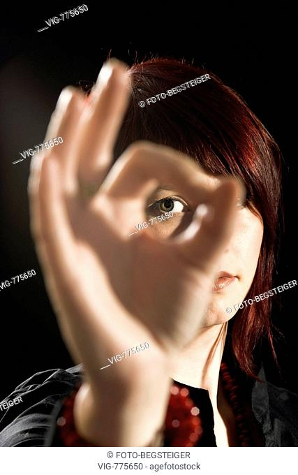 woman looks through fingers - 30/04/2008