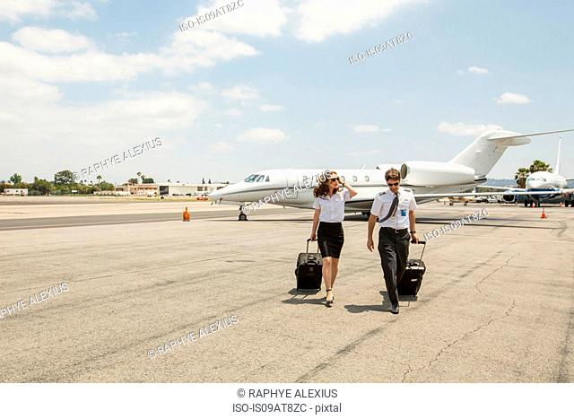Male and female private jet pilots arriving at airport