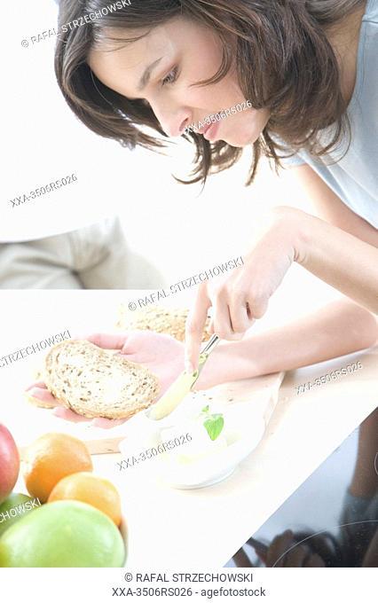 woman buttering bread