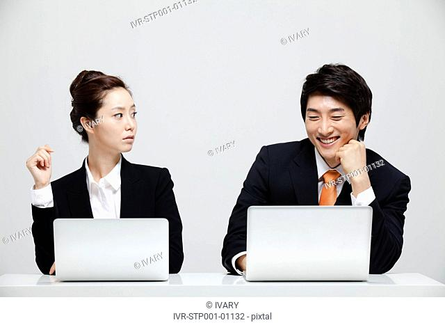 Asian Businesswoman Looking At Cheering Businessman Sitting At Desk With Laptop