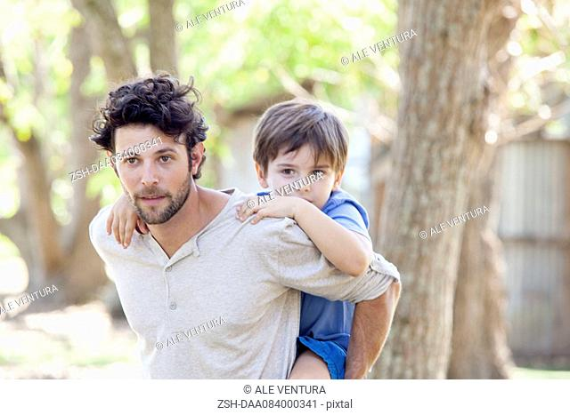 Father carrying young son piggyback