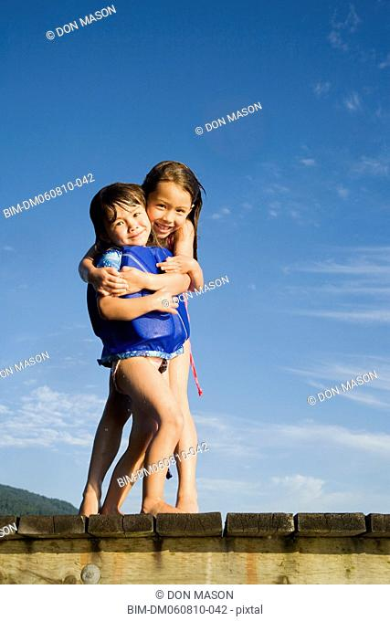 Young Asian sisters hugging on dock