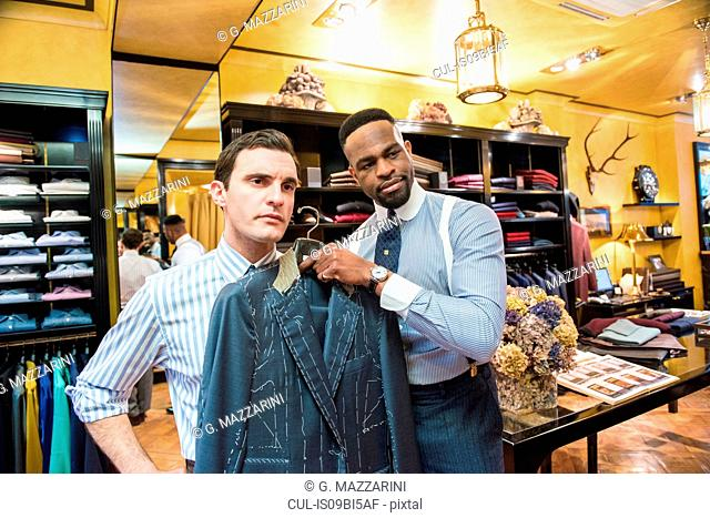Tailor holding bespoke suit jacket against customer in tailors shop