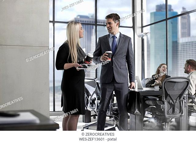 Businessman with coffee talking to woman in city office