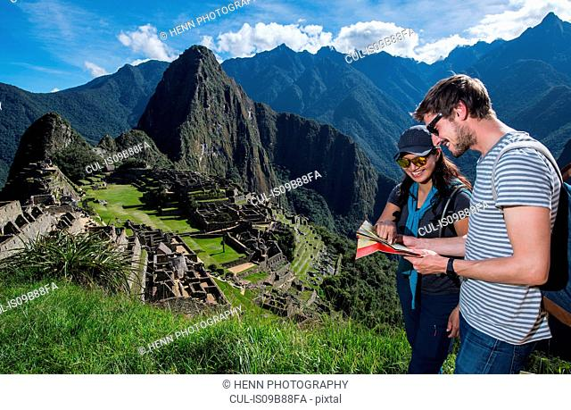 Couple at Inca ruins looking at folding map, Machu Picchu, Cusco, Peru, South America