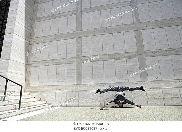 Young acrobatic businessman doing headstand and split while using laptop