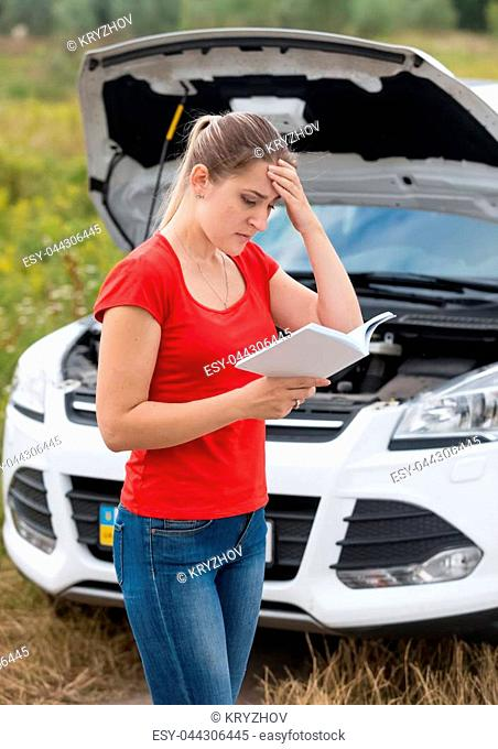 Portrait of upset woman reading manul for her broken car in field
