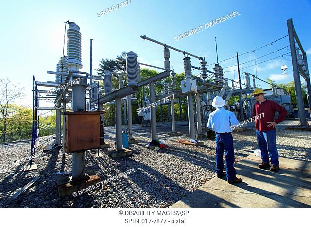 Power engineers reviewing maintenance at high voltage power distribution station, Braintree, Massachusetts, USA