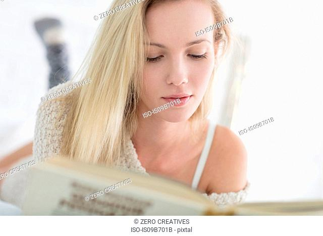 Young woman lying on bed, reading book