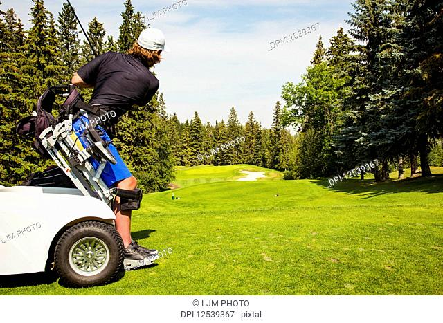 A physically disabled golfer using a specialized wheelchair teeing off and driving a ball down the fairway of a golf course; Edmonton, Alberta, Canada