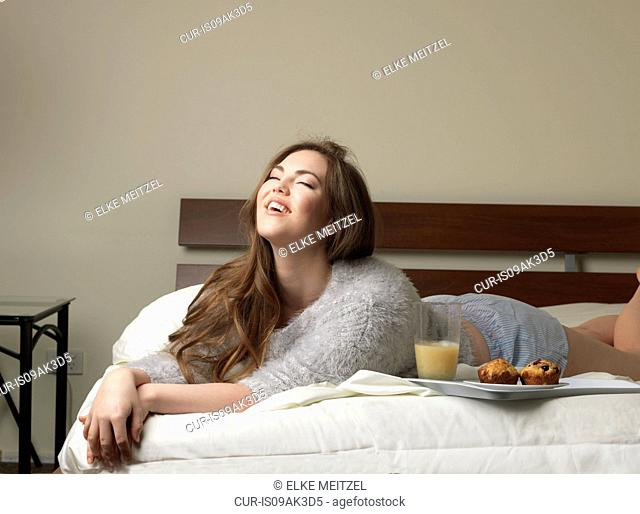 Beautiful young woman laughing on hotel bed