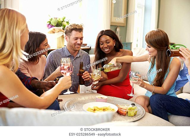 Group Of Friends Relaxing At Home With Drinks Together