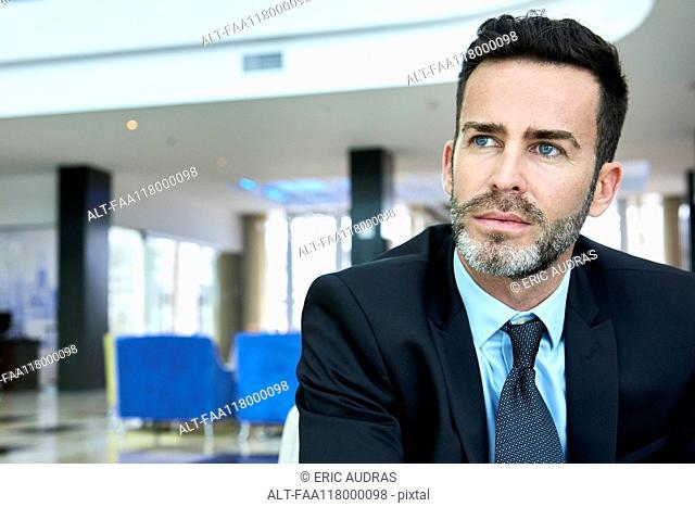 Thoughtful businessman sitting on sofa
