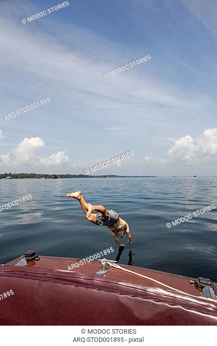Man Jumping From An Antique Wooden Boat In The Saint Lawrence River