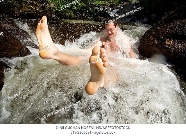 Man sitting in a rushing stream, countryside of northern Sweden