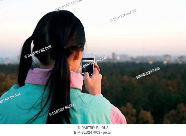 Woman photographing scenic view with cell phone