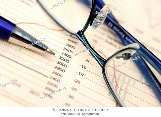 Glasses and pen on economic report
