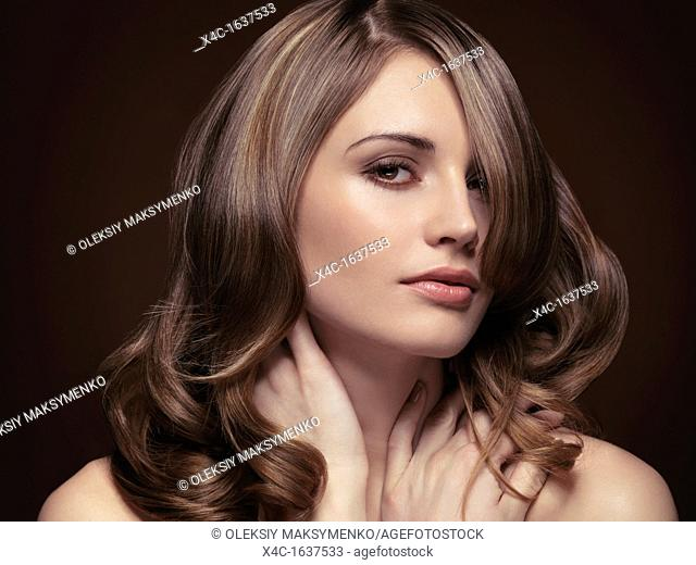 Sensual beauty portrait of a young beautiful woman on dark brown background